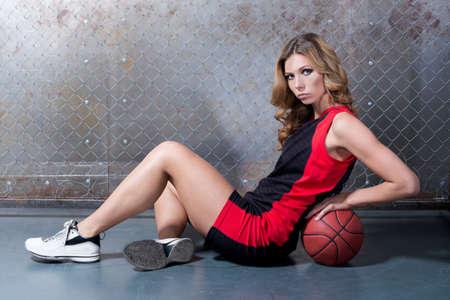 baloncesto chica: Mujer en la presentación del suelo con la bola de la cesta Foto de archivo