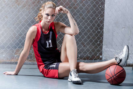 Woman on floor posing with the basket ball photo