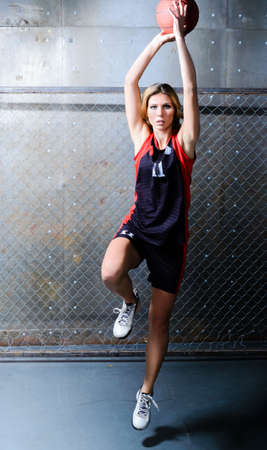 Throwing in jump. Professional basketball player in motion. photo