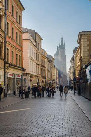 クラクフ、ポーランド - 2015 年 11 月 3 日: 2015 年 11 月 3 日にポーランドのクラクフでの後ろに Mariacka 教会の尖塔とスタンダード ・ ダブル通り