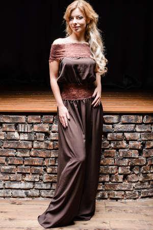 dark interior: Young woman portrait in brown dress at dark interior