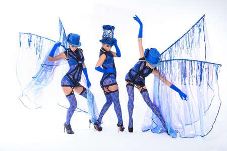 go go dancer: Dancing women trio in blue dresses. Studio perfomance.