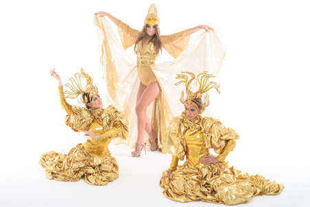 perfomance: Dancing women trio in golden dresses. Studio perfomance. Stock Photo