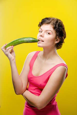 joyfull: Girl is playing with cucumber on colored background. Natural unretouched image.