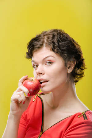 joyfull: Girl with red apple on colored background. Natural unretouched image.