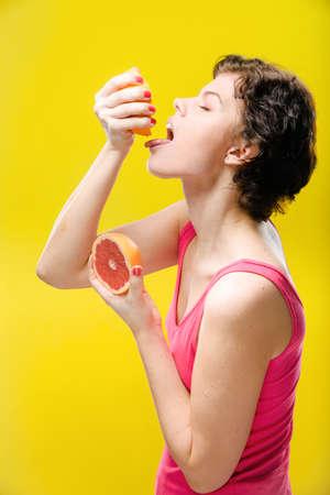 色付きの背景に赤いグレープ フルーツ スライスを持つ少女。自然の未修整画像。