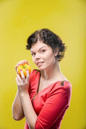色付きの背景に黄色の唐辛子を持つ少女。自然の未修整画像。