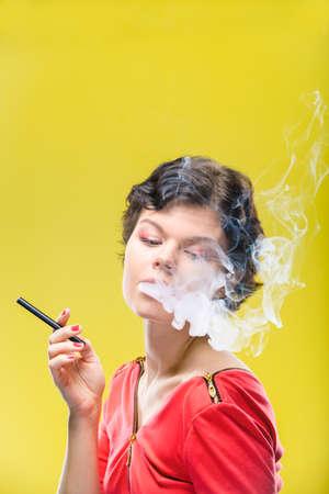 黄色の背景に電子タバコを持つ少女。補正後の画像。