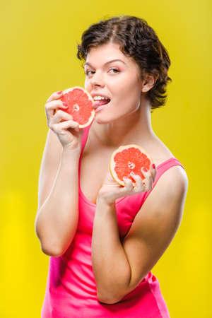 黄色の背景上のグレープ フルーツのスライスを持つ少女。補正後の画像。