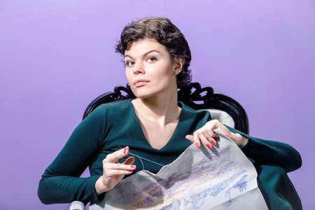色付きの背景に椅子の上仕事を編み物を持つ少女。補正後の画像。 写真素材