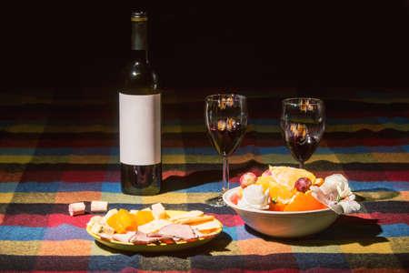 オレンジ、グレープ色の毛布で覆われたテーブルをワインの瓶に添え、 写真素材