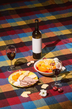 colored bottle: Served table with wine bottle, orange and grape covered with colored blanket