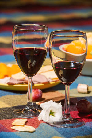 ワイングラス、オレンジ、グレープ色の毛布で覆われたテーブルを添え