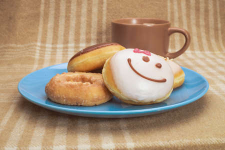 Sweet breakfast with mug of coffee and several donuts