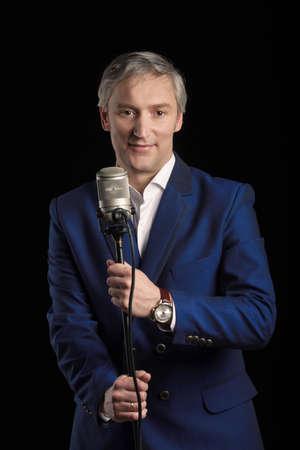 マイクと紺のスーツの地位に歌手 写真素材