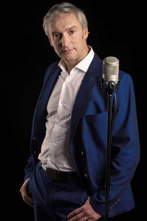 hoary: Singer in blue suit standing with microphone