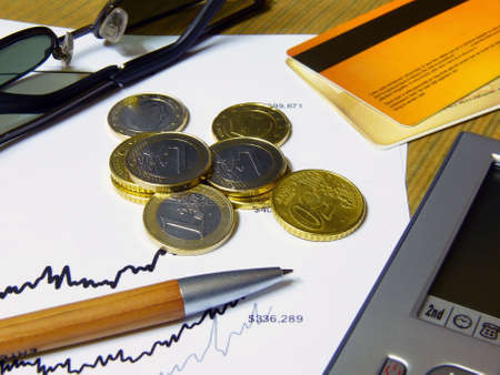 creditcards: Some European coins, wooden pen, pda and sunglasses lying on top of a chart Stock Photo