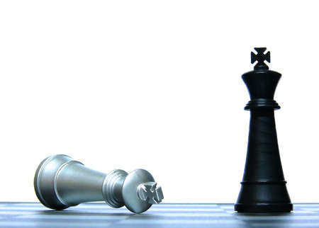 Victorious black king and Defeated white king in a chess game conceptually depicting defeat and victory photo