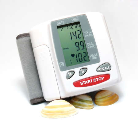 millimetres: Closeup of a blood pressure measuring device supported by some seashells