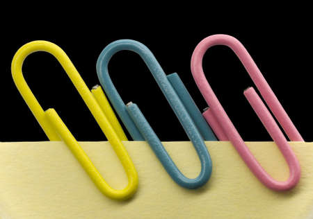 Paperclips on a yellow note with black background photo