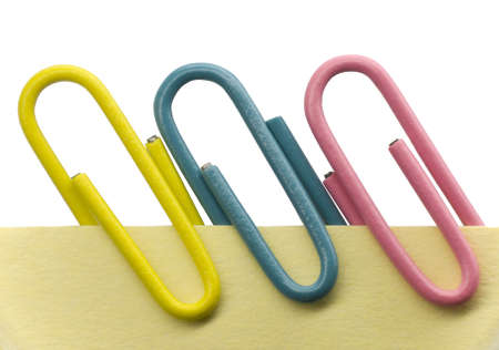 Paperclips on a yellow note with white background photo