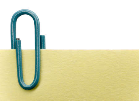 Blue paperclip on a yellow note with white background photo