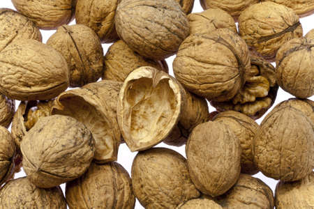 Whole walnuts and cracked walnuts as background texture but on a white surface photo
