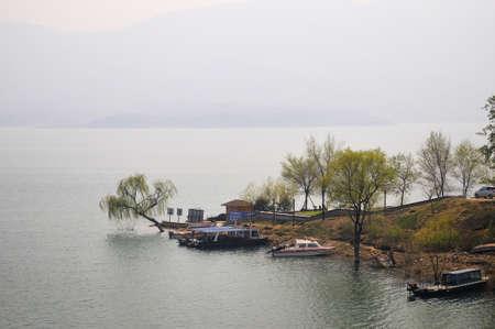 The lake has a marina, while several yachts moored. photo