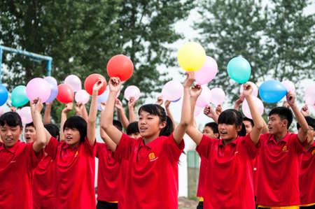 venues: Baixiang County, Hebei Province, China, May 13, 2013. Student Games held in the local school playground, the opening ceremony, athletes jubilation into sports venues. Editorial