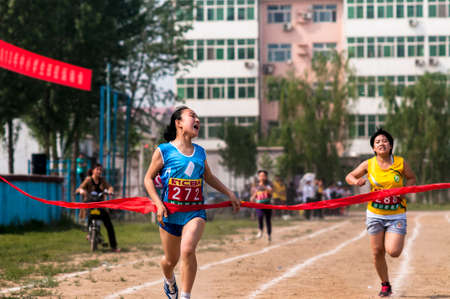 strive: Baixiang County, Hebei Province, China, May 13, 2013. Student Games track race finish, athletes strive first, toward the finish line.