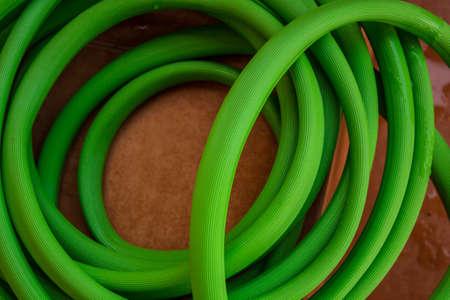 Green hose reel on tile
