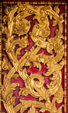 thai pattern carve with gold color and red background photo