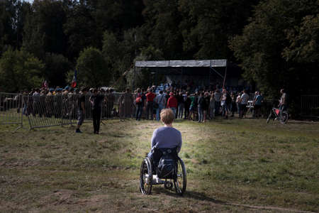 A woman with disabilities watches a crowd of people