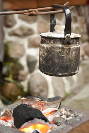 the kettle is suspended over the embers. Camping.