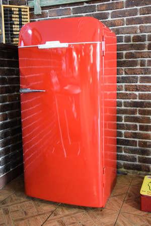 Vecchio frigorifero vintage rosso, in un ambiente naturale. Antiquariato attuale. Bar. Archivio Fotografico