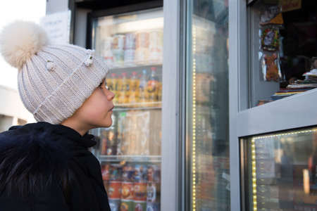 A child in winter clothes attentively examines the window of a street kiosk.