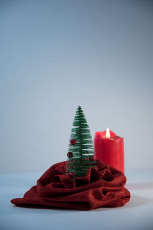 A Christmas tree peeking out of a bag. Toy Christmas tree. Christmas tree in a bag. Christmas composition. red candle in the background.