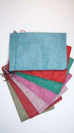 用不同的颜色包装礼物的织品袋子,在白色背景。袋子堆叠在一起。包装由粗麻布,不同的颜色制成。