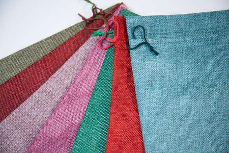 用不同的颜色包装礼物的织品袋子,在白色背景。袋子堆叠在一起。包装由粗麻布,不同的颜色制成。心形花边。