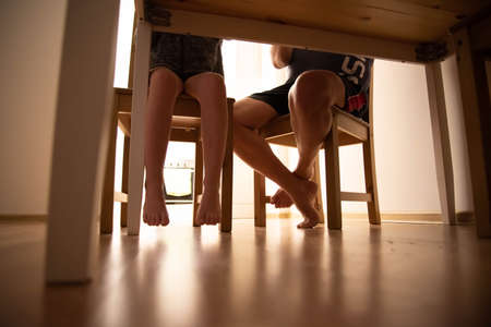 Concept. The photo was taken under the table. You can see the legs of the father and child, who are sitting at the table.