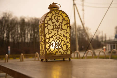 The lamp with a warm yellow light softly illuminates the space around. The lantern stands on the table of a street cafe, creating a cozy space around. The lamp has fanciful fairy-tale patterns.