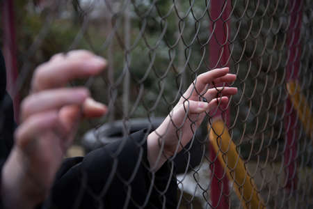 little girl hand holding on chain link fence for freedom, Human Rights Day, child labor, violence concept. Standard-Bild