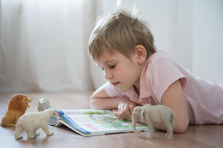 A pretty blond kid with a short haircut is reading a huge book. The preschooler sat on the warm floor. Nearby are placed toys, animals and dinosaurs, which carefully read the story. An elephant, a polar bear, a rhinoceros, and a lion are placed next to the book. Cozy and happy home environment.