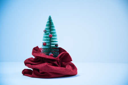 A Christmas tree peeking out of a bag. Toy Christmas tree. Christmas tree in a bag. Christmas composition. Stock Photo