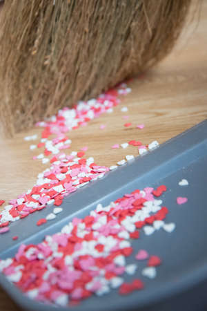 Concept: to deal with feelings, to kill love. Cleaning small colorful hearts. A broom and dustpan.