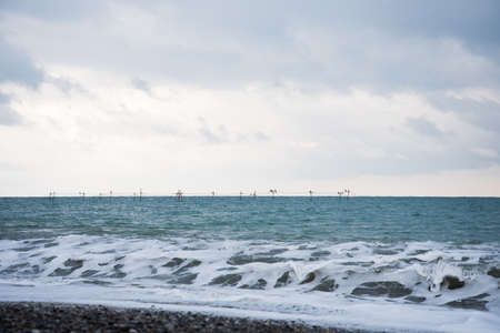 A small oyster and mussel farm on The black sea coast. Farm structures are visible in the sea, and a wave storm 4 points Is in the foreground. The light sky sets off the color of the sea.