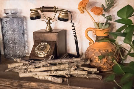 Antique telephone set in a natural setting. There are vases of flowers around. Old.