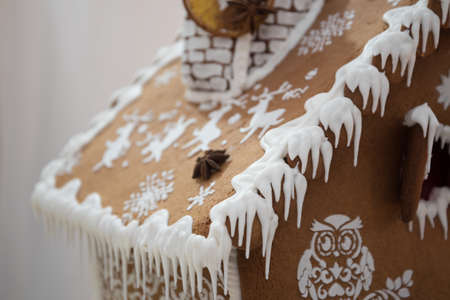 Element of a Christmas gingerbread house, the roof is decorated with icing. White icicles hanging from the roof of a gingerbread house.