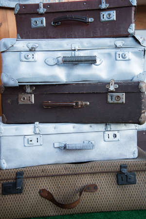 Vintage weathered leather and metal suitcases on top of each other. Retro. Background, structure.