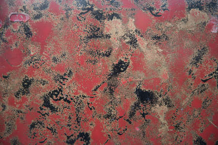 Cracked enamel surface of the hood of the old car was painted yellow and black and red colors. The concept of vintage texture. background